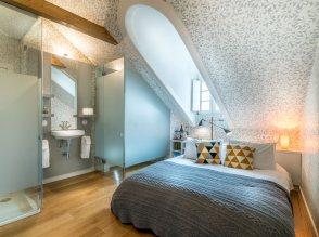 quarto-silvestre-com-cama-espelho-e-casa-de-banho